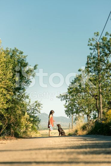 stock-photo-95308969-girl-with-pet-dog-walking-along-road-in-countryside