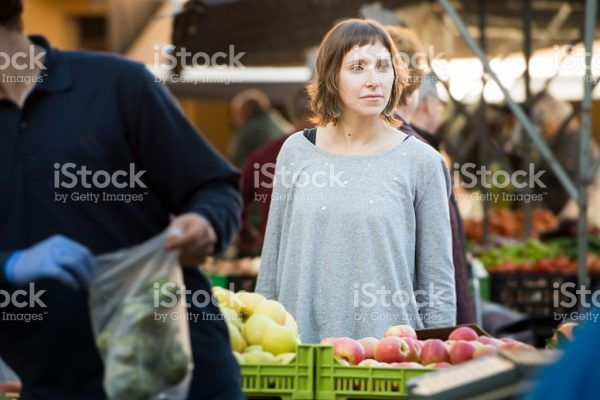 Young woman from Mallorca, Spain, buying at farmer's market organic food for a healthy eating lifestyle.